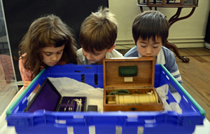 Three children looking at a box of object
