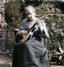 Self Portrait Colour Photograph of and by Sarah Acland. She sits in the foreground on a chair and is holding her guitar. It has been taken outside.