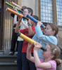 Children look through telescopes they have made in the 'Galileo's Telescope' workshop.