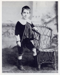 Family photograph of young Harry standing beside a chair
