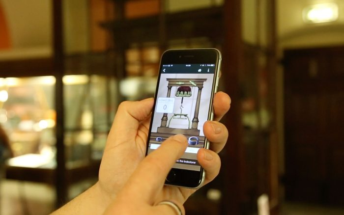 A photograph of two hands demonstrating the lodestone animation within the Pocket Curator App